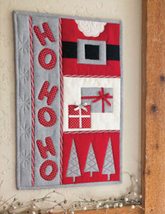 The Ho Ho Ho wall hanging, which is a quilt-as-you-go method shown in the video from The Quilting Company.