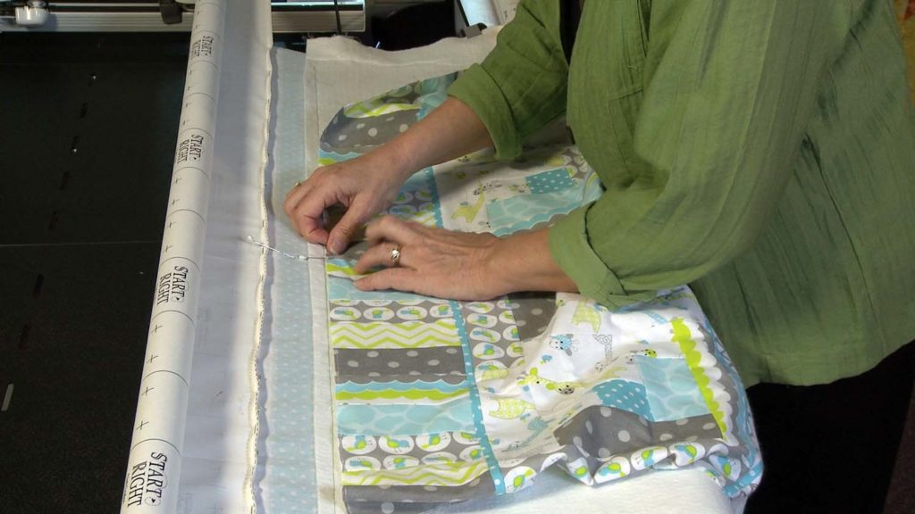 baste across the top and then down the sides of the quilt top