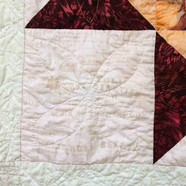 close-up of a portion of the quilt showing how the dark red batik bled into neighboring cream patches