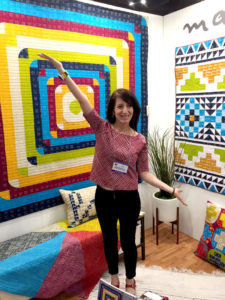 Malka Dubrawsky at Quilt Market next to one of her creations