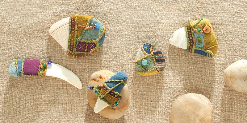 Talismans made from cloth, beads, and found shells by Victoria Gertenbach from the cover of Quilting Arts Magazine