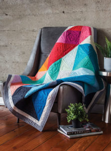Create the appearance of a stained glass window with this modern quilt featuring Half-Square Triangle and Quarter-Square Triangle blocks.