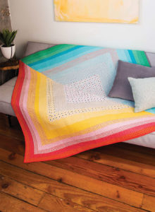 This modern quilt by Malka Dubrawsky is crafted out of an oversized Half-Square Triangle block consisting of strip piecing