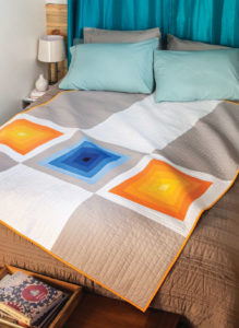 Improv Log Cabin-style blocks create movement in this modern quilt.