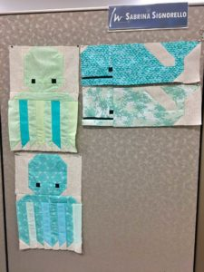 Blocks from Elizabeth Hartman's Awesome Oceans pattern, affixed to my cubicle walls