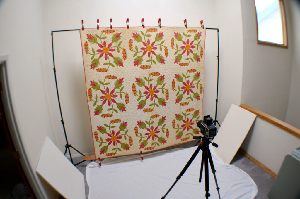 Quilt photography set up of studio view with quilt hanging on stand.