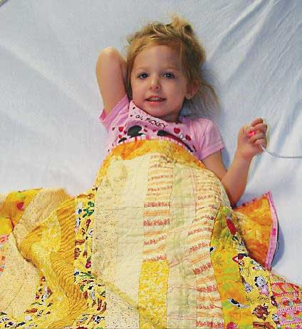 Little girl with the yellow patchwork quilt donated by Quilts for Kids
