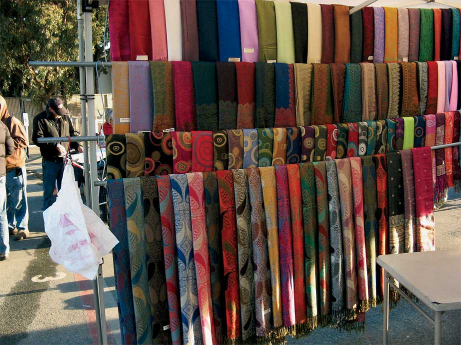 A row of pashmina shawls offered for sale at the Santa Cruz Flea Market