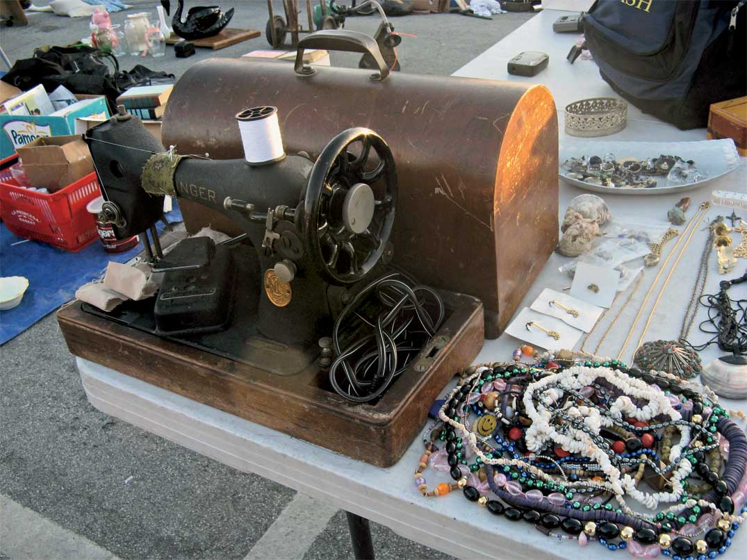 A Singer Featherweight with carrying case next to a pile of junk jewelry at the Santa Cruz Flea Market.