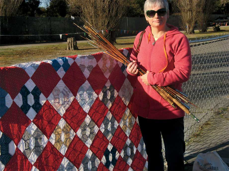 Pam Rocco's friend Carolyn at the Flea, holding some old fishing rods and standing next to a 75˝ x 86˝ bowtie quilt top with an unusual setting that she bought for $15. The bowtie blocks were handpieced, but the blocks and on-point setting squares were sewed together by machine. The fabrics (red, blues, gold, gray, mourning prints) are in good shape and look to be about 100 years old.