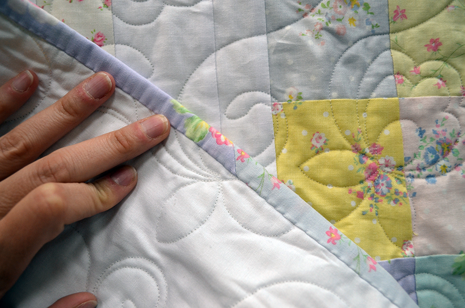This quilt binding is pieced from leftover pre-cut strips, and is secured to the back with an elegant whipstitch.
