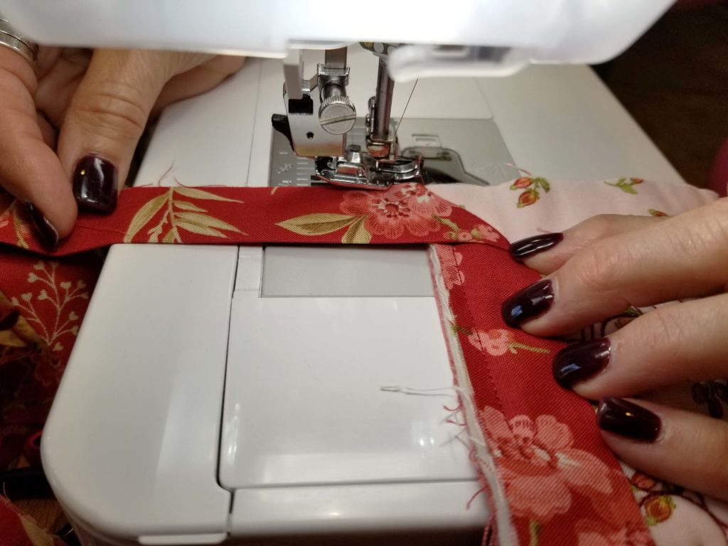 Lori demonstrates the quilt binding method she learned from her mother
