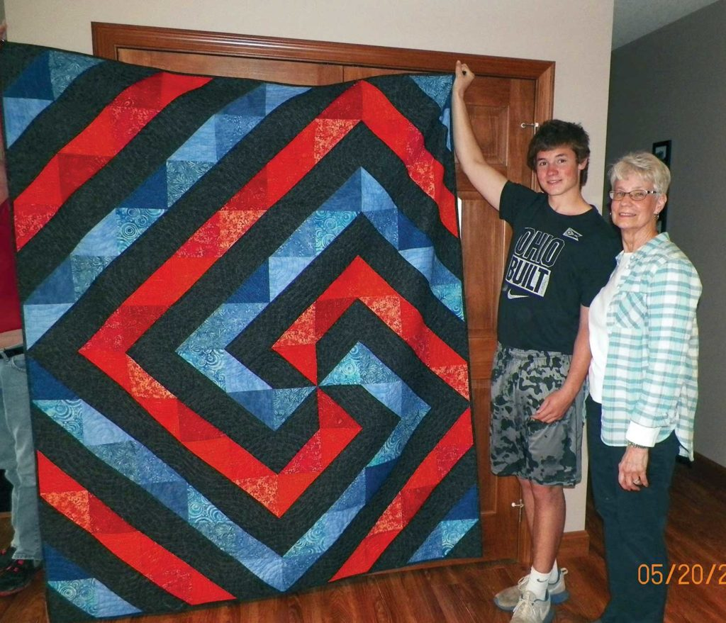 Joyce VanAtta with grandson Joel display her version of the Cartwheels pattern from McCall's Quick Quilts.