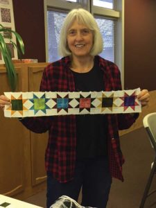 Claudia Kniffin of the UFOers of Denver with the star blocks she made for A Bitty Christmas.