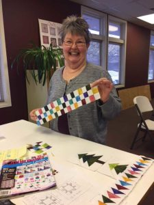 Judy Barry of the UFOers of Denver with the checkerboard row she made for A Bitty Christmas.