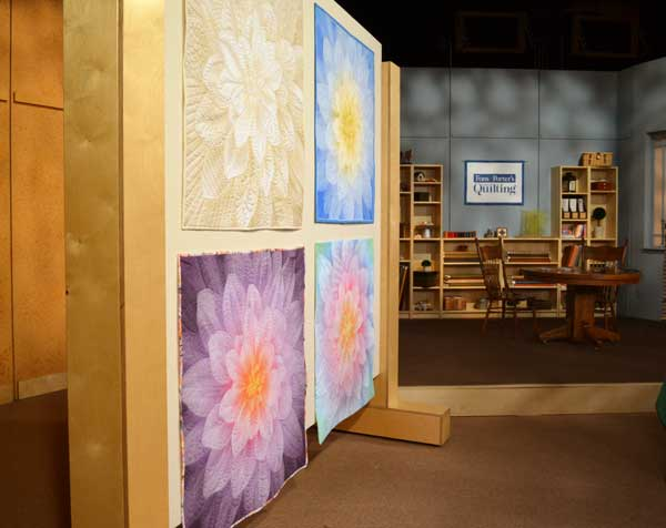 The set of Love of Quilting burst into bloom on the longarming show, episode 3309 Using Panels for Practice.
