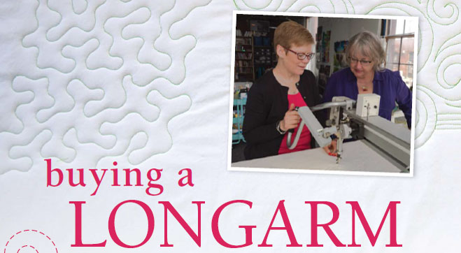 Timna Tarr showing an editor of Quilting Arts how to longarm a quilt.